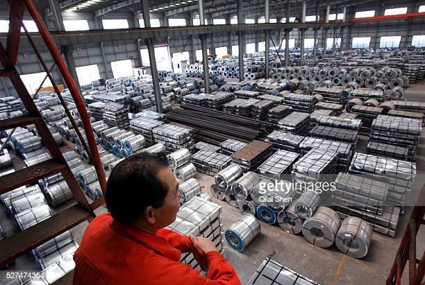 A crane operator looks onto a floor filled with steel products as he takes a break on a perch at a warehouse run by the Shanghai Yirong Trading...