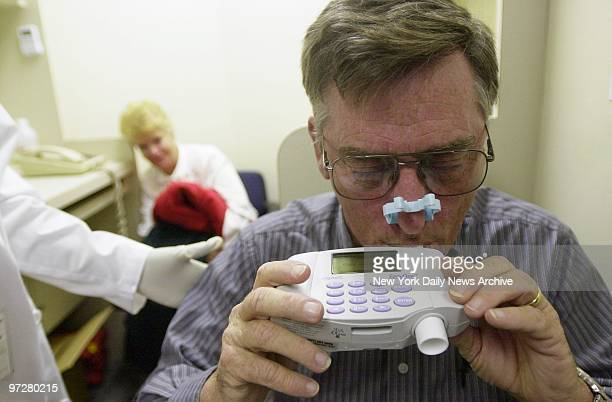 Crane operator Stephen Nolan takes a breathing test to check lung function as his wife Peg watches at a medical screening clinic for World Trade...