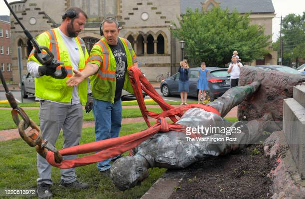 Crane operators hook up the remains of the Richmond Howitzers statue of a Confederate artilleryman. It was pulled down by protesters last night;...