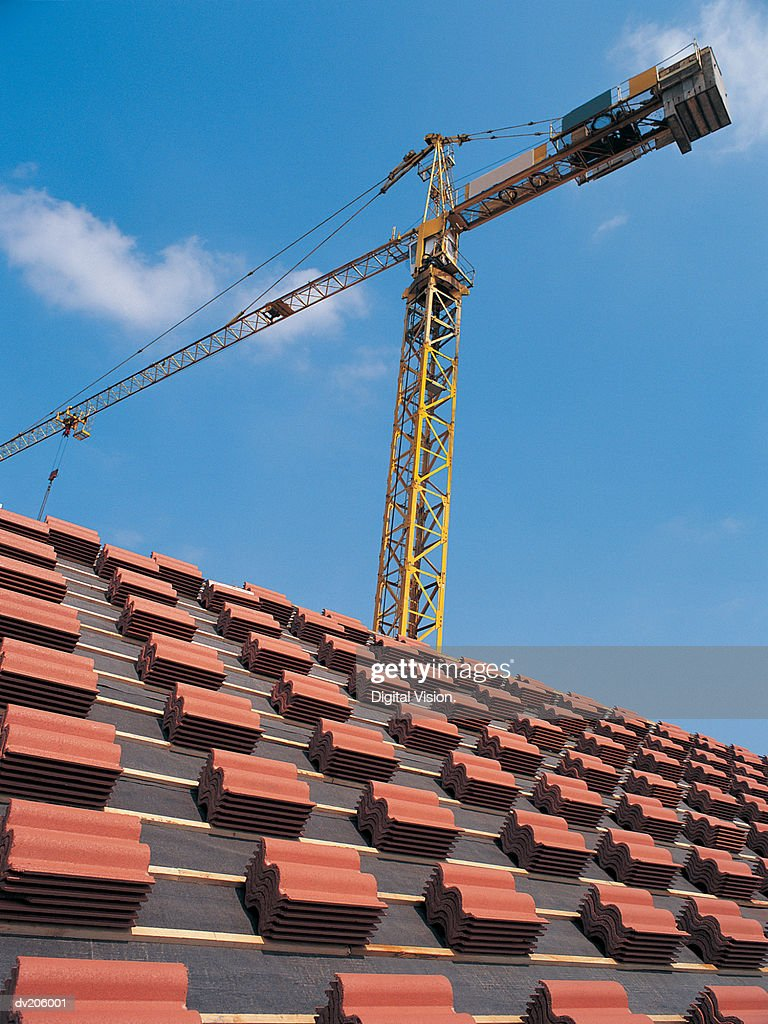 Crane positioned behind rooftop : Stock Photo