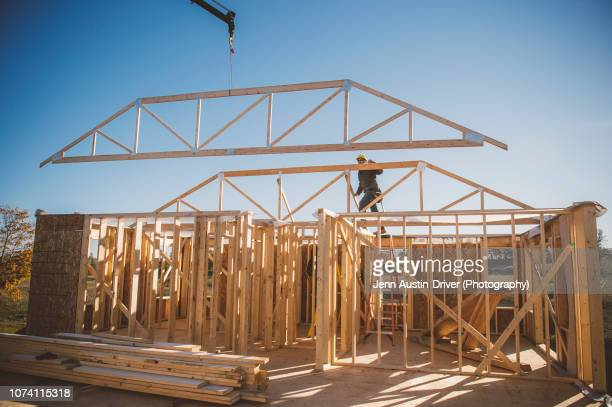 crane positioning frame over building - construction frame stock pictures, royalty-free photos & images