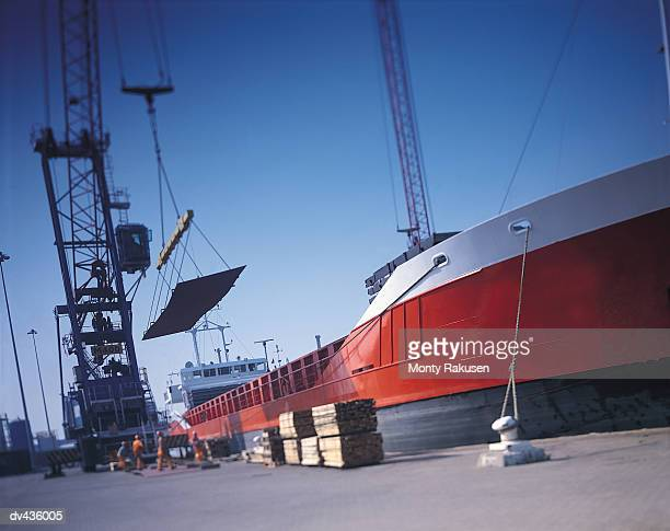 crane putting cargo onto ship - moored stock pictures, royalty-free photos & images