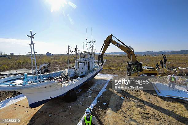 A crane removes structures from the deck of a fishing boat on November 21 2014 in Namie Fukushima Japan Work got under way to demolish and remove...