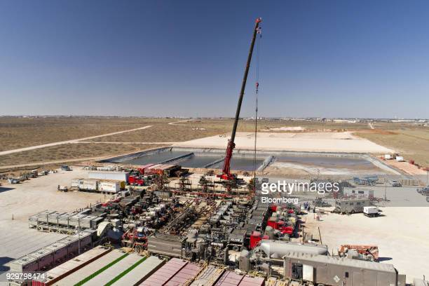 A crane secures a wireline a cable used to lower and raise tools and other equipment in a well shaft above one of six Chevron Corp oil wells being...