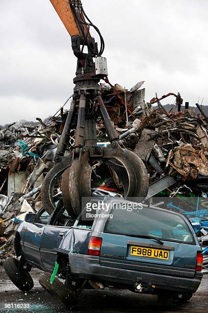 A crane shatters the windows of a car to be scrapped while lifting it at the CMS Automotive Solutions scrap yard in Gloucester UK on Monday March 29...