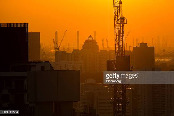 A crane standing at the construction site is silhouetted at dusk in Singapore on Thursday Sept 15 2016 Singapore is currently mired in its most...