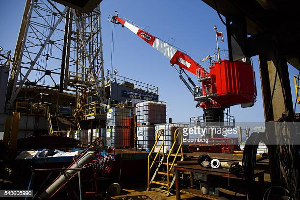 A crane stands near equipment stores on the Casablanca oil platform operated by Repsol SA in the Mediterranean Sea off the coast of Tarragona Spain...
