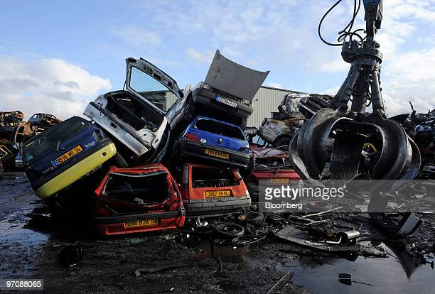 A crane swings by piles of damaged cars at Allo Casse Auto's car demolition site in Athis Mons France on Wednesday Feb 24 2010 French consumer...
