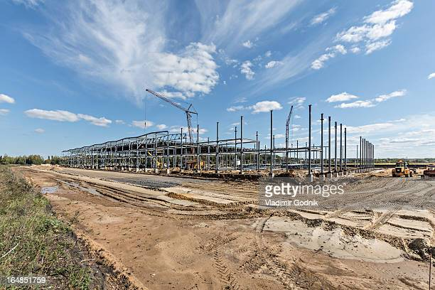a crane towering above a construction frame at a construction site - construction site stock pictures, royalty-free photos & images