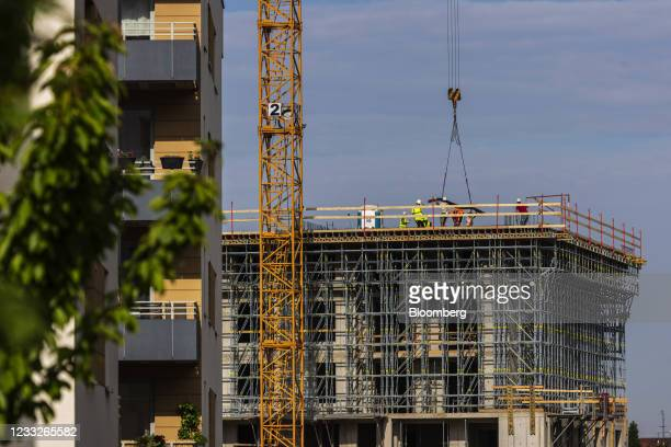 Crane transports steel reinforcement rods at a residential apartment block construction site, on a plot of brownfield land in the Vysoany district in...