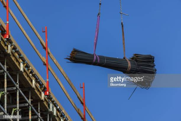 Crane transports steel reinforcement rods at a residential apartment construction site, on a plot of brownfield land in the Vysoany district in...