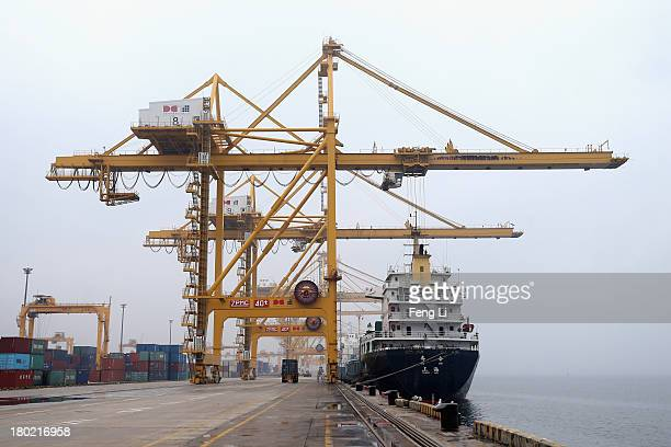 A crane unloads a shipping container from a vessel at Port of Dalian on September 10 2013 in Dalian of Liaoning Province China China's exports rose...