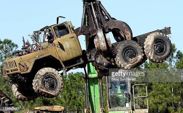 A crane unloads one of the wellknown Soviet Block military trucks that have been sitting on US 49 in Saucier for years into the yard at Alter Metal...