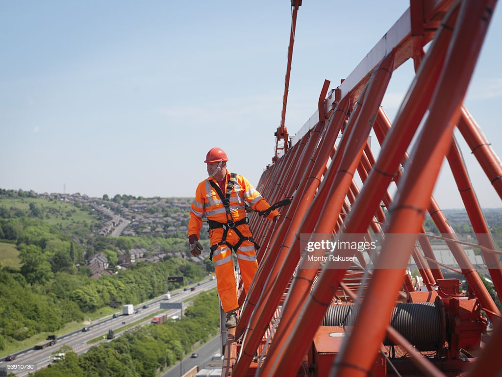 Crane Worker On Arm Of Crane : Stock Photo