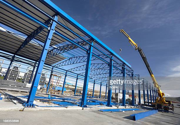 a crane working on a factory building - built structure stock pictures, royalty-free photos & images