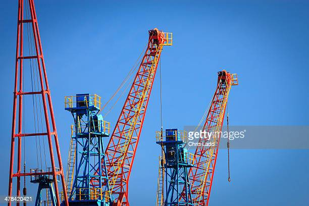 Cranes against clear blue sky