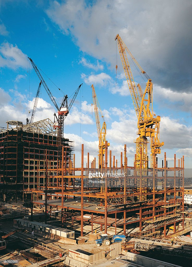 Cranes among scaffolding and framework : Stock Photo