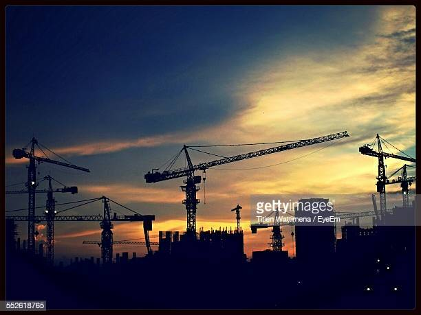 Cranes And Buildings Silhouetted Against Dusky Sky
