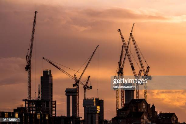 cranes and construction equipment on london city skyline - crane stock pictures, royalty-free photos & images