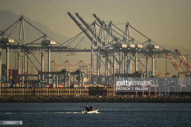 Cranes and stacks of cargo shipping containers stand at the Port of Los Angeles on October 15, 2021 in San Pedro, California. - The port, North...
