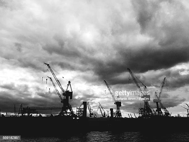 Cranes At Commercial Dock Against Cloudy Sky