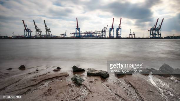 cranes at commercial dock against sky - sandra gygax stock-fotos und bilder