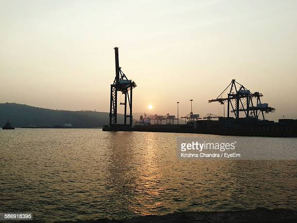 cranes at commercial dock in sea against sunset sky - ヴィシャカパトナム ストックフォトと画像