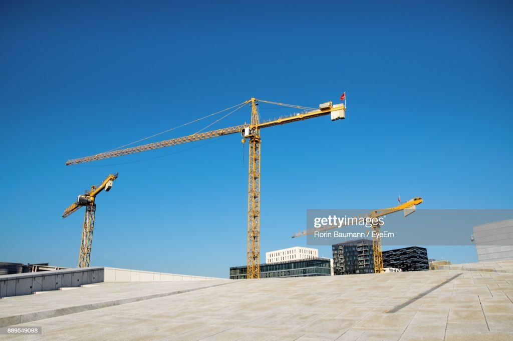 Cranes At Construction Site Against Clear Blue Sky : Stock Photo