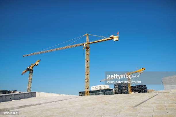 cranes at construction site against clear blue sky - kran stock-fotos und bilder