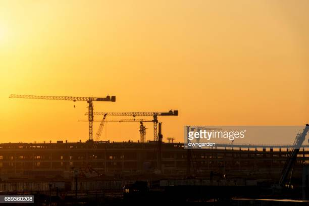 Cranes at construction site at sunset