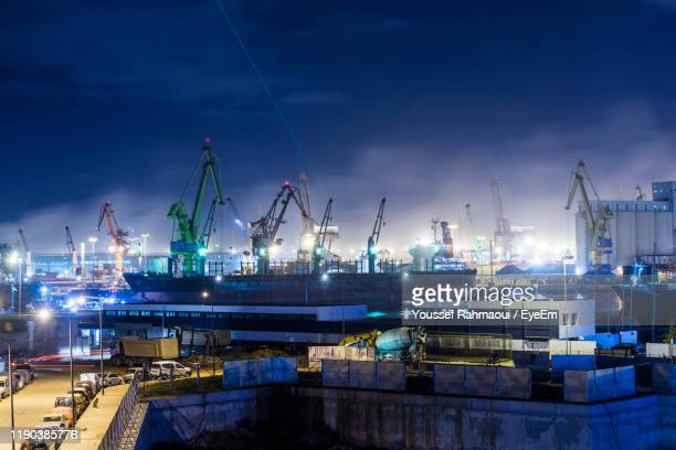 cranes at harbor against sky at night - casablanca morocco stock pictures, royalty-free photos & images
