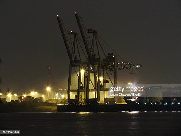 Cranes At Illuminated Commercial Dock Against Clear Sky At Night