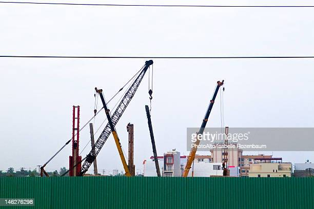 Cranes behind corrugated metal fence