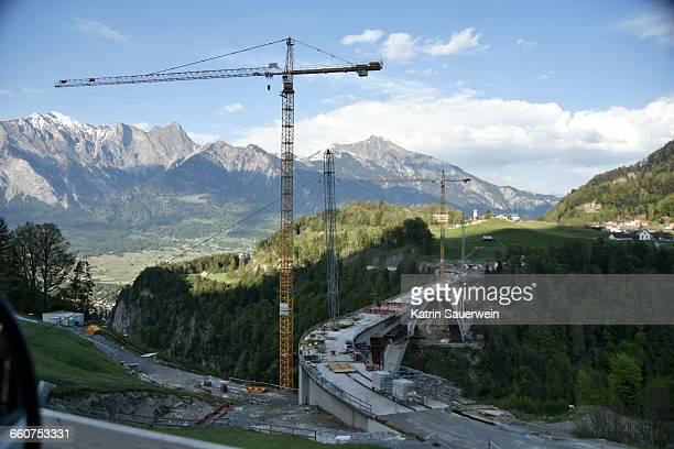 cranes by bridge during construction - bridge built structure stock photos and pictures