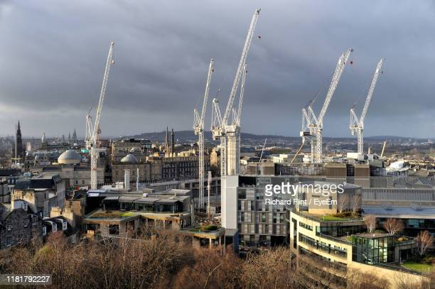 cranes by buildings at construction site against sky - richard flint stock pictures, royalty-free photos & images