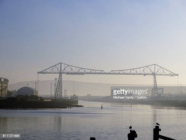 cranes by sea against clear sky - vardy stock photos and pictures