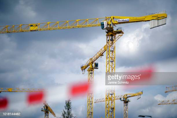 BERLIN GERMANY AUGUST Cranes for house construction are pictured behind a barrier tape on August 10 2018 in Berlin Germany