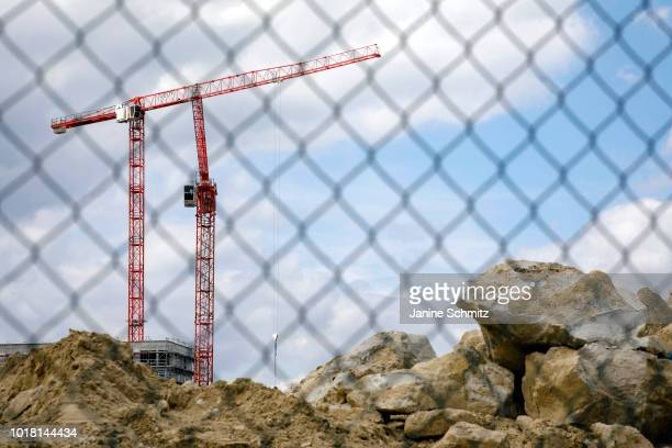 BERLIN GERMANY AUGUST Cranes for house construction are pictured behind a wiremesh fence on August 10 2018 in Berlin Germany