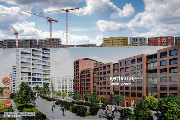 BERLIN GERMANY AUGUST Cranes for house construction are pictured next to new and old residential properties behind an information wall about the...
