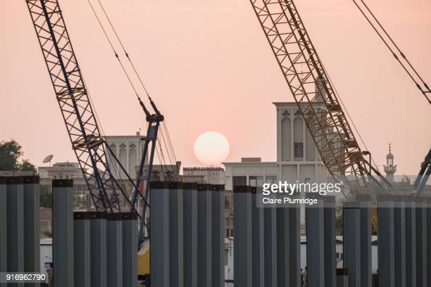 cranes loading and unloading from cargo ships, in dubai creek, united arab emirates. taken at dusk. - claire plumridge stock pictures, royalty-free photos & images