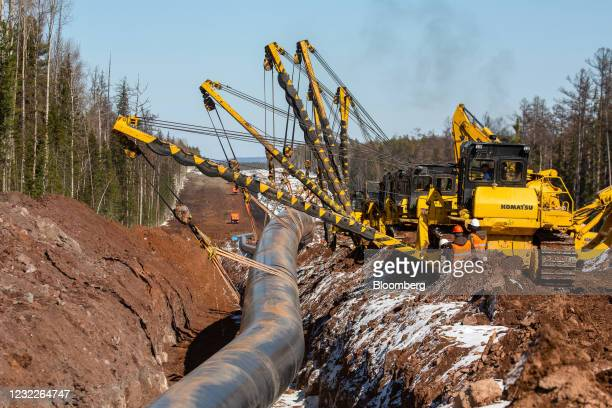 Cranes lower joined sections of pipework into a trench during pipeline laying operations for the Gazprom PJSC Power of Siberia gas transmission line...