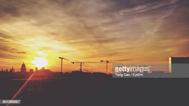 Cranes On Silhouette Landscape At Sunset