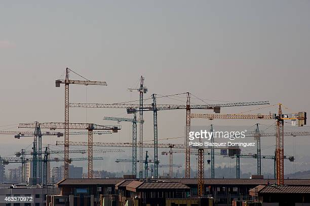Cranes operate at a construction site on February 13 2015 in Madrid Spain Spain's residential property sales rose during 2014 for the first time in...