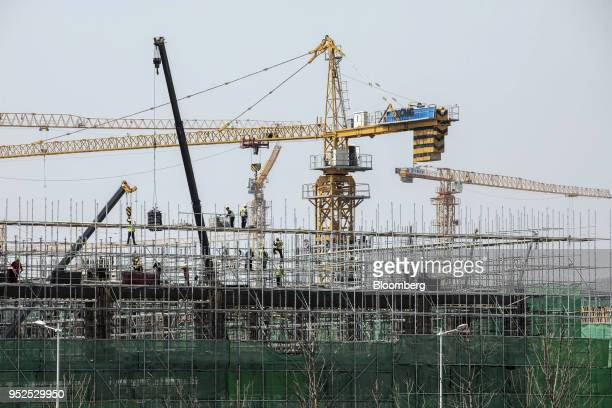 Cranes operate at residential buildings under construction at the Dalian Wanda Group Co Oriental Movie Metropolis film production hub in Qingdao...