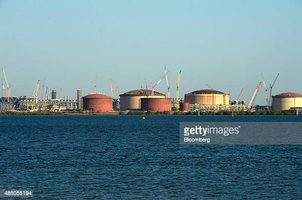 Cranes operate near Liquefied natural gas storage tanks in Darwin Australia on Wednesday July 29 2015 Australia's dollar dropped toward a sixyear low...