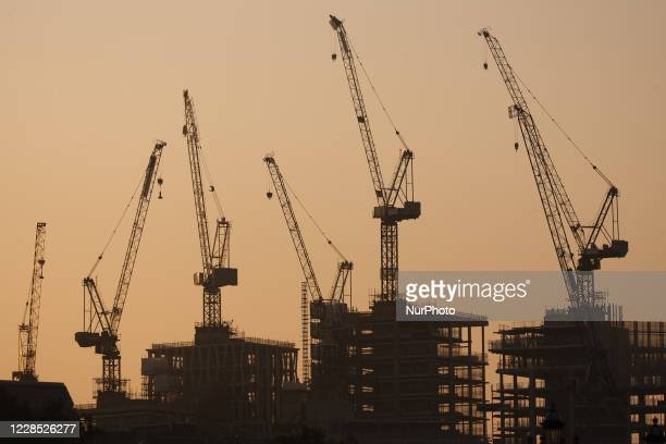 Cranes rise from a new buildings under construction in the Victoria neighbourhood of the City of Westminster at dawn in London, England, on September...