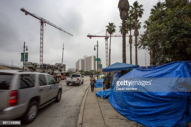 Cranes rise over a construction site near sidewalk homeless encampments on May 1 2017 in Los Angeles California The newly released 2017 Greater Los...
