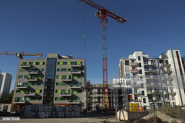 Cranes stand among newlycompleted apartment buildings in the city center on September 22 2016 in Berlin Germany Berlin real estate prices are...
