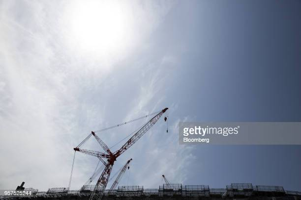 Cranes stand at the construction site of the New National Stadium a venue for 2020 Summer Olympics and Paralympics in Tokyo Japan on Friday May 11...