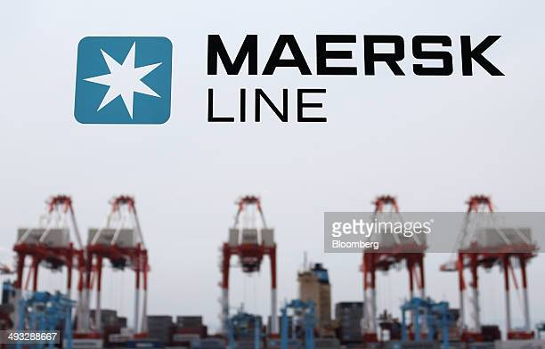 Cranes stand behind the logo of Maersk Line operated by AP MoellerMaersk A/S displayed on a glass door at the company's container yard in Yokohama...